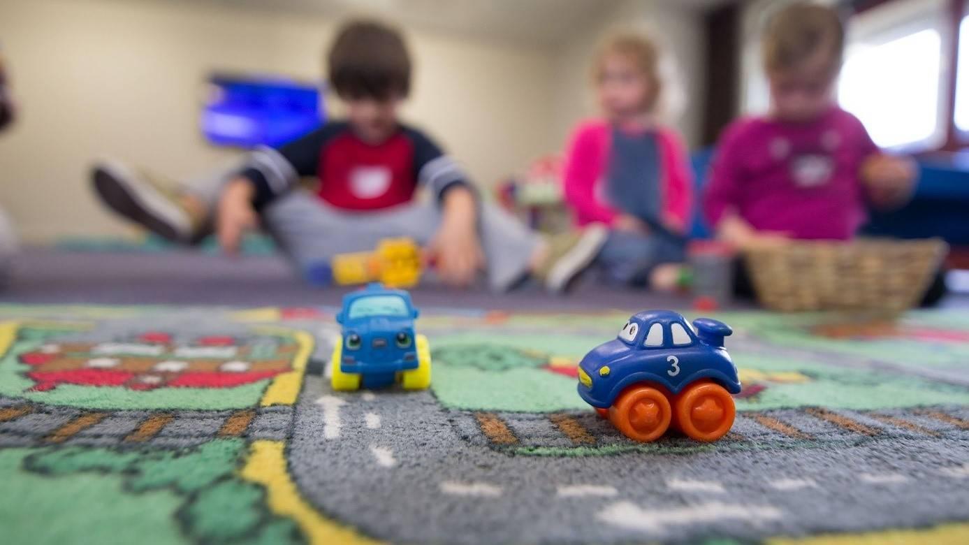 drei spielende Kinder in einem Raum mit zwei farbigen Spielzeugautos