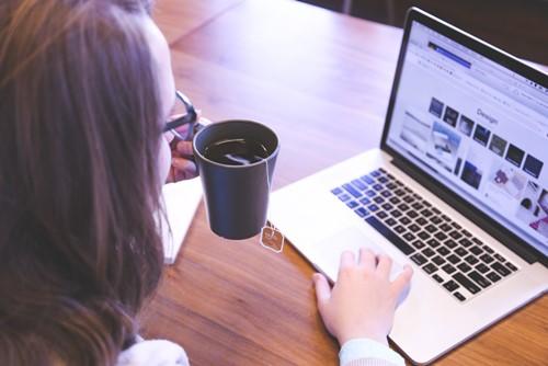 kita leitungskraft arbeitet am laptop mit einer Tasse Tee in der linken hand