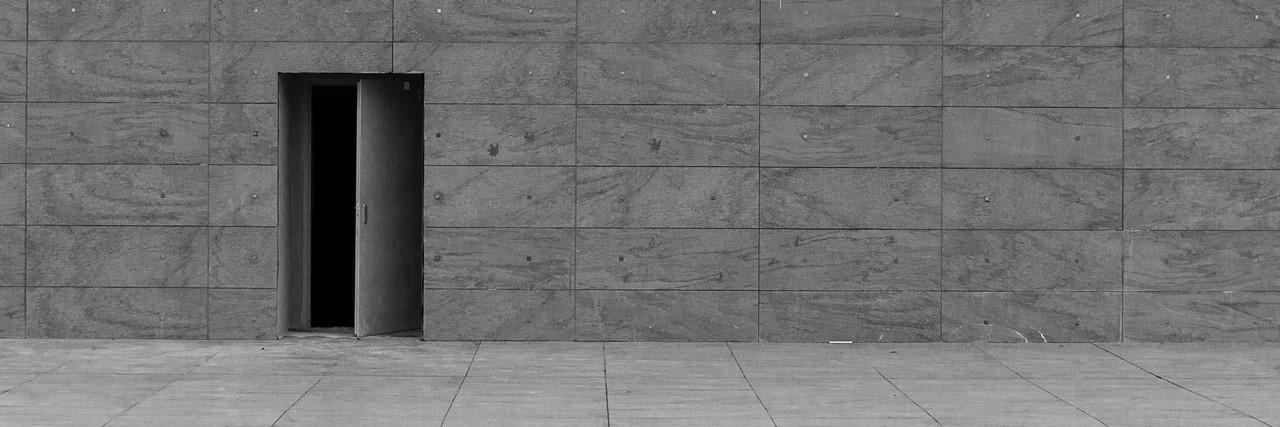 offene tuer in einer wand mit steinfassade als symbol fuer die ungewissheit bei der kommenden wiedereröffnung der kitas nach der corona-bedingten Schliessung