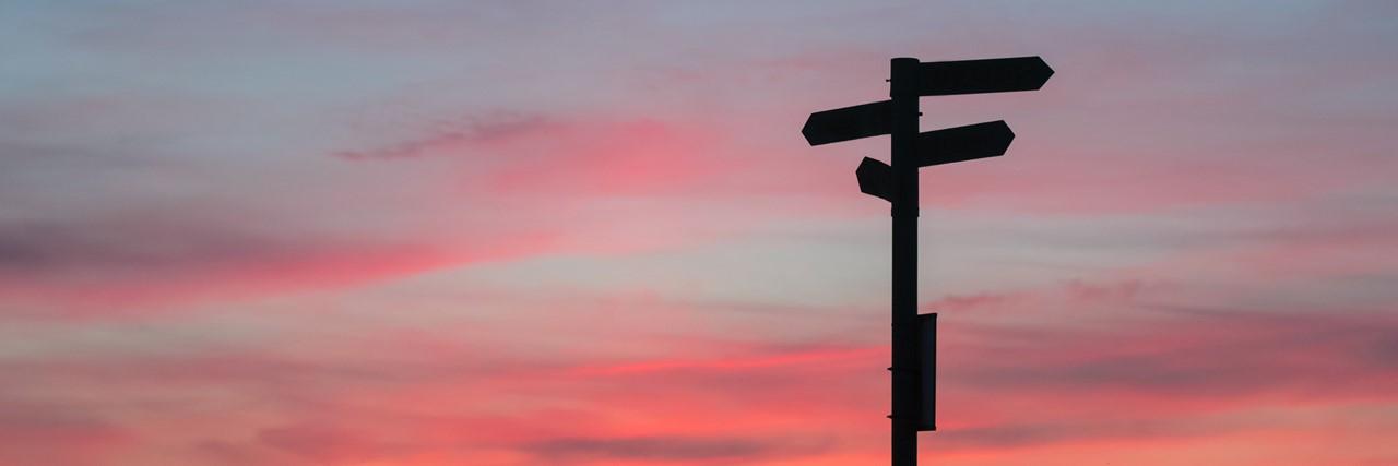 wegweiser mit schildern in unterschiedliche richtungen bei sonnenaufgang mit morgenrot fotografiert als symbol der möglichen veränderungen im kita-bereich zur wiedereröffnung nach der corano-bedingten schliessung