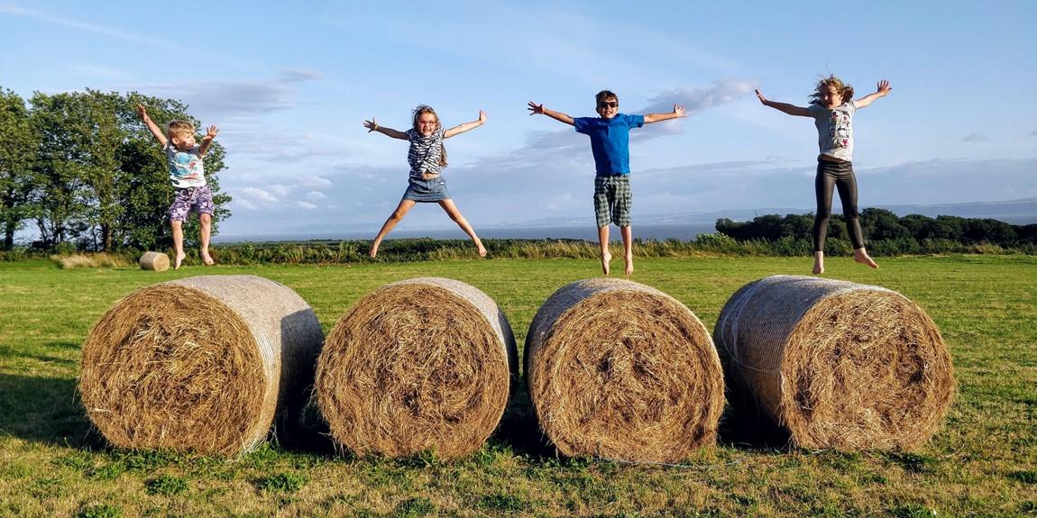 vier huepfende Kinder auf vier runden strohballen bei blauem himmel auf freiem feld als symbol fuer den bewegungsdrand von kindern
